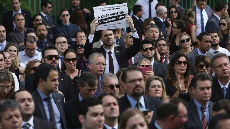 FILE - In this Dec. 1, 2016, file photo, public prosecutor employees from various states protest lawmakers' attempt to pass legislation that would allow judges and prosecutors to be charged with abuse of authority, in Brasilia, Brazil. Congress launched an around-the-clock session seeking to gut anti-corruption legislation the same day people learned of the air disaster that killed 71 people, including almost an entire soccer team, spurring violent protests in the capital of Brasilia. (AP Photo/Eraldo Peres, File)