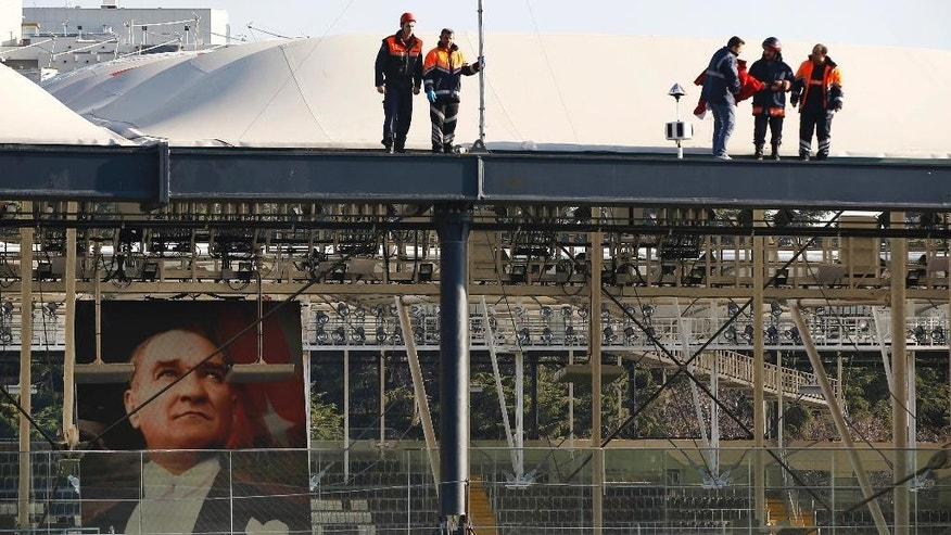 Firefighters work on the roof of the Besiktas football club stadium Vodafone Arena as a poster of modern Turkey's founding father Mustafa Kemal Ataturk is seen on the wall in Istanbul, Sunday, Dec. 11, 2016 following the late Saturday explosions. Turkey declared a national day of mourning Sunday after twin blasts in Istanbul killed dozens of people and wounded many others near the soccer stadium — the latest large-scale assault to traumatize a nation confronting an array of security threats. (AP Photo/Emrah Gurel)
