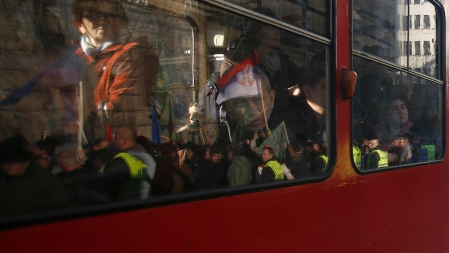 People look through the windows of a tram as it drives by the government building during a protest of Serbian police and army in Belgrade, Serbia, Sunday, Dec. 11, 2016. Several hundred members of the Serbian police and army have staged a protest complaining of low wages and poor living standards. (AP Photo/Darko Vojinovic)