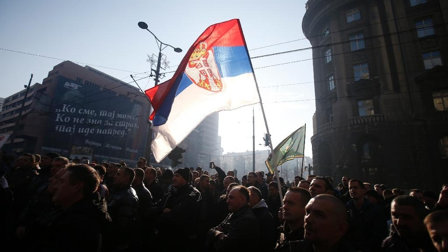 A protester holds a Serbian flag during a protest of Serbian police and army in Belgrade, Serbia, Sunday, Dec. 11, 2016. Several hundred members of the Serbian police and army have staged a protest complaining of low wages and poor living standards. (AP Photo/Darko Vojinovic)