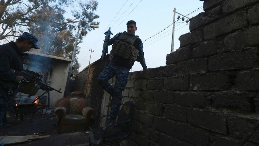 A policeman secures houses as Iraqi federal police forces advance towards the Islamic State militant held city of Mosul, Iraq, Saturday, Dec. 10, 2016. An Iraqi commander says reinforcements have been sent to eastern Mosul after a major Islamic State counterattack drove troops back last week, further slowing a nearly two-month-old offensive to retake the city. (AP Photo/Hadi Mizban)