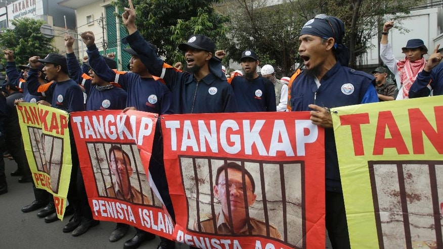 "Protesters display posters of Jakarta Governor Basuki Tjahaja Purnama, popularly known as ""Ahok,"" with writings that read: ""Arrest blasphemer"" during his trial hearing at a district court in Jakarta, Indonesia, Tuesday, Dec. 13, 2016. Ahok is on trial on accusation of blasphemy following his remark about a passage in the Quran that could be interpreted as prohibiting Muslims from accepting non-Muslims as leaders. (AP Photo/Achmad Ibrahim)"