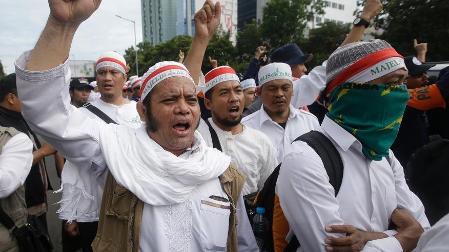 "Muslim Protesters shout slogans during a rally outside a court where the trial hearing of Jakarta Governor Basuki Tjahaja Purnama, popularly known as ""Ahok,"" is held in Jakarta, Indonesia, Tuesday, Dec. 13, 2016. Ahok is on trial on accusation of blasphemy following his remark about a passage in the Quran that could be interpreted as prohibiting Muslims from accepting non-Muslims as leaders. (AP Photo/Achmad Ibrahim)"