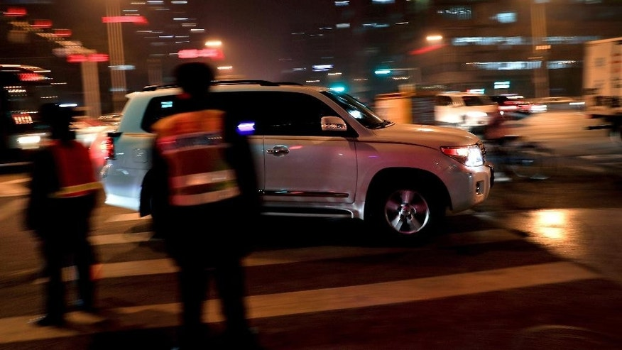 An SUV vehicle drives past traffic wardens during the evening rush hour in Beijing, Monday, Dec. 12, 2016. China's explosive demand for SUVs helped boost auto sales 17.2 percent in November over a year ago, an industry group said Monday, as automakers prepared for the end of a key tax break and a potential slump in demand. (AP Photo/Andy Wong)
