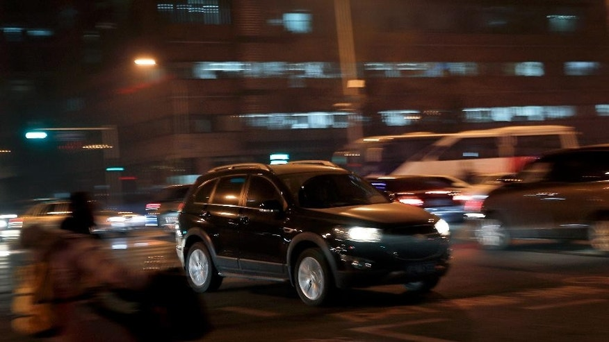 An SUV vehicle drives past a heavy traffic junction during the evening rush hour in Beijing, Monday, Dec. 12, 2016. China's explosive demand for SUVs helped boost auto sales 17.2 percent in November over a year ago, an industry group said Monday, as automakers prepared for the end of a key tax break and a potential slump in demand. (AP Photo/Andy Wong)
