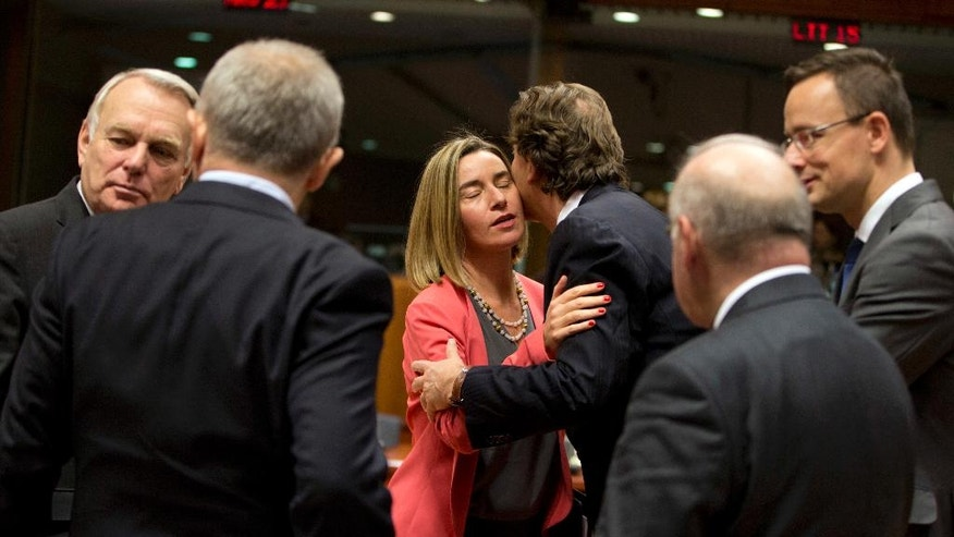 European Union High Representative Federica Mogherini, center left, is greeted by Dutch Foreign Minister Bert Koenders, center right, during a round table meeting of EU foreign ministers at the EU Council building in Brussels on Monday, Dec. 12, 2016. EU foreign ministers hold talks Monday on the conflict in Syria, relations with Africa and migration. (AP Photo/Virginia Mayo)