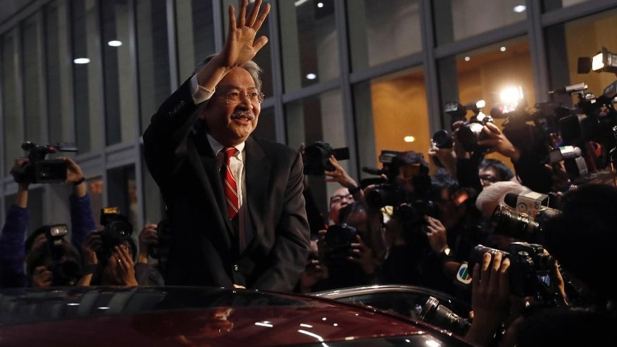 Hong Kong's Financial Secretary John Tsang waves to reporters as he leaves his office in Hong Kong, Monday, Dec.12, 2016. Tsang resigned on Monday, in what is widely seen as a prelude to a leadership bid for the southern Chinese city's top job. Tsang said he submitted his resignation to the current leader, Chief Executive Leung Chun-ying, who announced unexpectedly on Friday that he would not seek a second term in office. (AP Photo/Vincent Yu)
