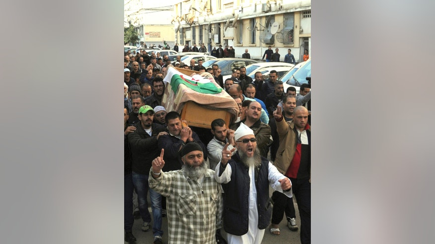 People carry the coffin of Algerian journalist, Mohamed Tamalt, during a funeral service in Algiers, Algeria, Monday, Dec. 12, 2016. On a hunger strike to protest a two-year sentence for offending President Abdelaziz Bouteflika, Tamalt has died in a hospital in the capital. (AP Photo/Sidali Djarboub)
