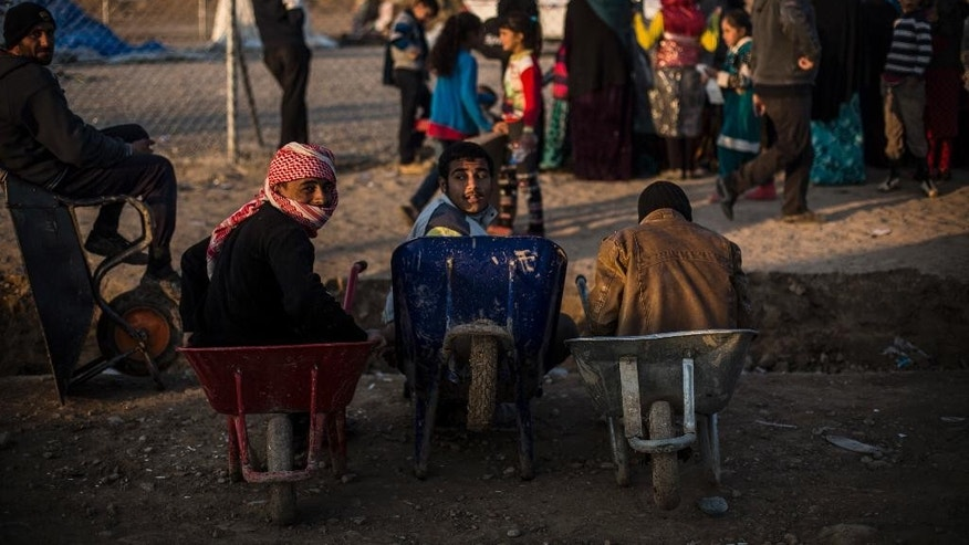 Iraqi youth sit in a wheelbarrow in Khazer camp for the displaced, Iraqi Kurdistan, Iraq, Monday, Dec. 12, 2016. A new report criticizes the U.S.-led coalition against IS for their lack of transparency when assessing civilian casualties. (AP Photo/Manu Brabo)