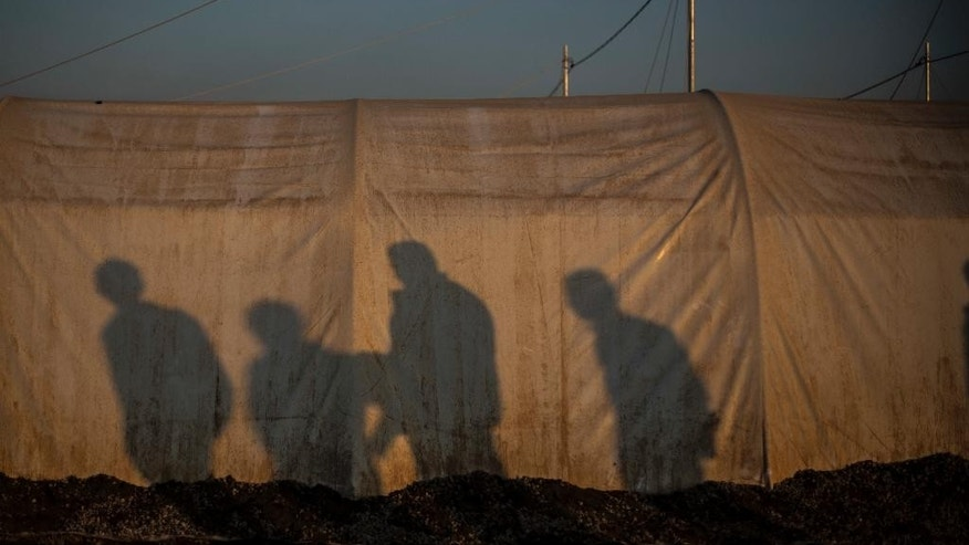 Shadows of Iraqi men in a tent at Khazer camp for the displaced, Iraqi Kurdistan, Iraq, Monday, Dec. 12, 2016. A new report criticizes the U.S.-led coalition against IS for their lack of transparency when assessing civilian casualties. (AP Photo/Manu Brabo)