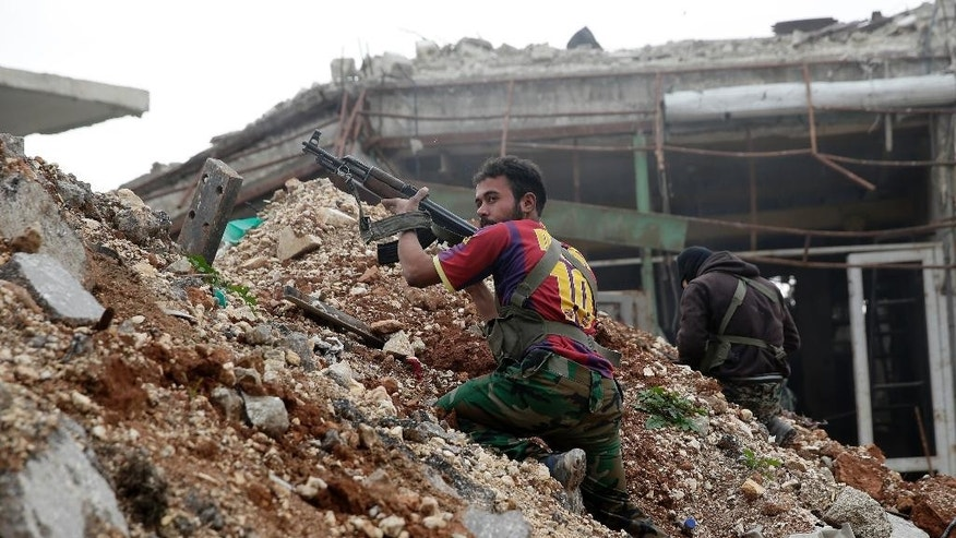 In this Monday, Dec. 5, 2016 photo, Syrian army soldiers fire their weapons during a battle with insurgents at the Ramouseh front line, east of Aleppo, Syria. The Syrian military said on Monday, Dec. 12, 2016, that it had gained control of 98 percent of eastern Aleppo, previously a rebel-held enclave, leaving only a small sliver of territory in the city packed with rebels and civilians who are being squeezed under fire. (AP Photo/Hassan Ammar)