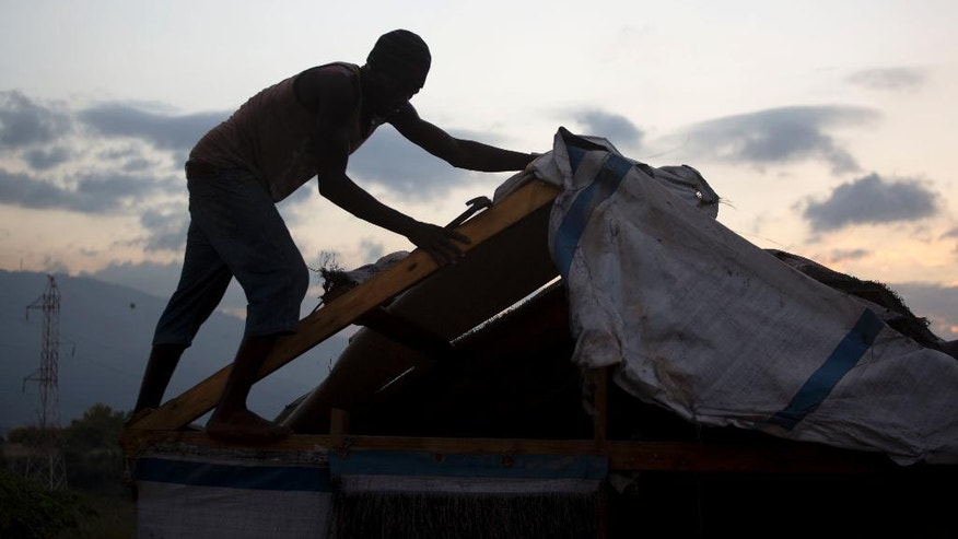In this Dec. 2, 2016 photo, a man breaks downs his shelter in the Delmas tent camp set up nearly seven years ago for people displaced by the 2010 earthquake, in Port-au-Prince, Haiti. The man has agreed to resettle and move into a one-year rental provided by the International Organization for Migration. (AP Photo/Dieu Nalio Chery)