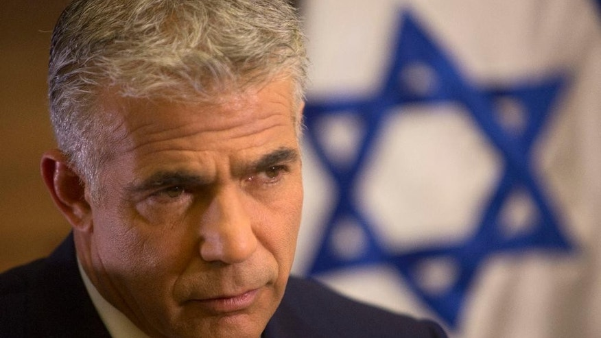 File - In this Monday, Oct. 31, 2016 file photo, Israeli Knesset member, Yair Lapid, leader of the Yesh Atid party, gives an interview to The Associated Press, in his office at the Knesset, Israel's parliament, in Jerusalem. Lapid, leading Israeli opposition politician is questioning Prime Minister Benjamin Netanyahu's goal of dismantling the international community's nuclear deal with Iran. Lapid told foreign reporters Monday that while he also does not like the deal, it may be too late to stop it. (AP Photo/Sebastian Scheiner, file)