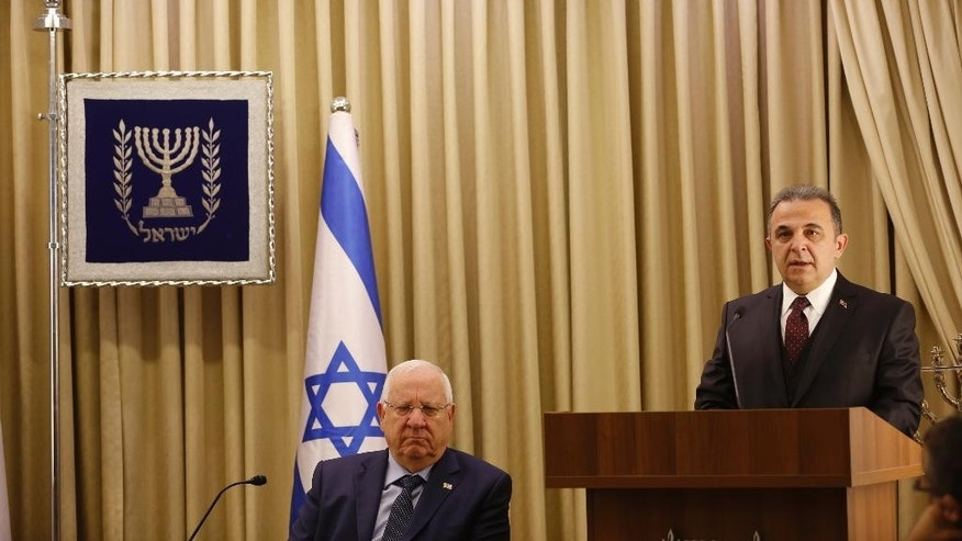Turkish ambassador to Israel Kemal Okem, right, speaks next to Israeli President Reuven Rivlin during a ceremony to present his diplomatic credentials, at the president's official residence in Jerusalem, Monday, Dec. 12, 2016. Turkey and Israel sent new ambassadors to each other's countries this month as part of a reconciliation deal to end six years of animosity. Relations imploded in 2010 after a confrontation between Israeli commandos and a Turkish flotilla trying to breach the blockade of Gaza that killed 10 Turkish activists. (Ronen Zvulun, Pool via AP)