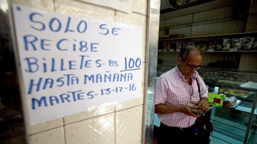 "A man counts his 100-bolivar notes next to a sign alerting customers with a message in Spanish that reads: ""100-bolivar notes will only be received until Tuesday, 12-13-16,"" inside a bakery in downtown Caracas, Venezuela, Monday, Dec. 12, 2016. Venezuelans are rushing to spend their 100-bolivar notes after a surprise announcement that they will be taken out of circulation this week. President Nicolas Maduro said on Sunday that his government would be pulling the bills to stop the ""mafias"" who smuggle contraband on the Colombian border. (AP/Photo/Fernando Llano)"