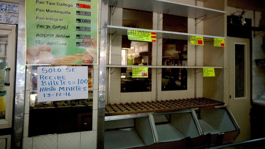 "A sign alerting customers with a message in Spanish reads: ""100-bolivar notes will only be received until Tuesday, 12-13-16,"" inside a bakery in downtown Caracas, Venezuela, Monday, Dec. 12, 2016. Venezuelans are rushing to spend their 100-bolivar notes after a surprise announcement that they will be taken out of circulation this week. President Nicolas Maduro said on Sunday that his government would be pulling the bills to stop the ""mafias"" who smuggle contraband on the Colombian border. (AP/Photo/Fernando Llano)"