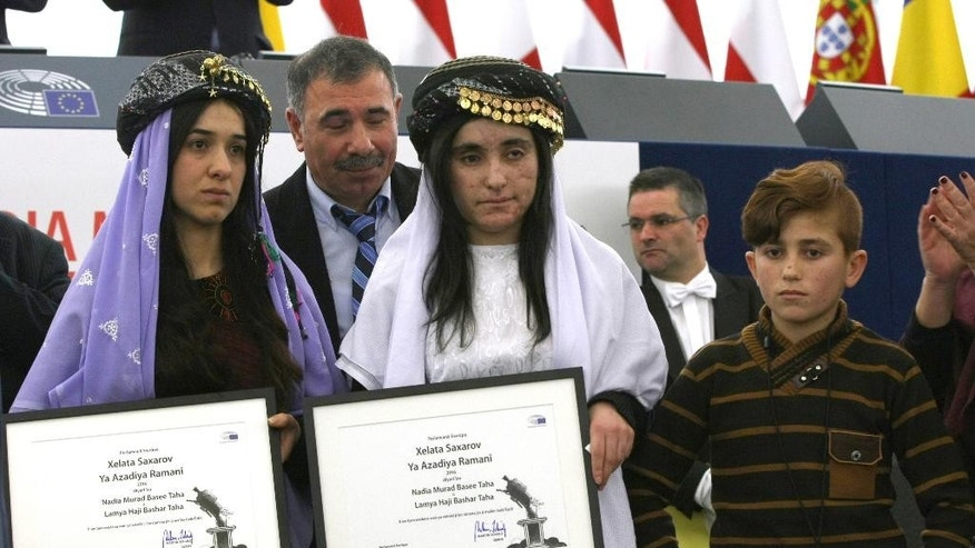 Yazidi women from Iraq, Nadia Murad Basee, left, and Lamiya Aji Bashar, pose with their award while Bashar's brother Vad, right, looks on after receiving the European Union's Sakharov Prize for human rights from the hands of European Parliament President Martin Schulz, right, at the European Parliament in Strasbourg, eastern France, Tuesday Dec. 13, 2016. Two Yazidi women who escaped sexual enslavement by the Islamic State group and went on to become advocates for others have won the European Union's Sakharov Prize for human rights. The award, named after Soviet dissident Andrei Sakharov, was created in 1988 to honor individuals or groups who defend human rights and fundamental freedoms. (AP Photo/Christian Lutz)
