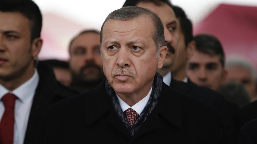 Turkey's President Recep Tayyip Erdogan attends the funeral prayers for police officer Hasim Usta, who was killed with dozens of others late Saturday outside the Besiktas football club stadium Vodafone Arena, in Istanbul, Monday, Dec. 12, 2016. Turkey's police rounded up more than 100 members of a Kurdish political party on Monday as the country mourned the dozens killed in a bombing attack near an Istanbul soccer stadium. Turkish authorities have banned distribution of images relating to the Istanbul explosions within Turkey. (AP Photo/Emrah Gurel)