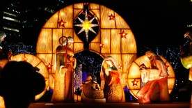 """A girl is silhouetted as she views a nativity scene known locally as """"Belen"""" displayed outside the Philippine Stock Exchange in Manila's Makati financial district December 21, 2010. REUTERS/Cheryl Ravelo (PHILIPPINES - Tags: SOCIETY RELIGION) - RTXVXLJ"""