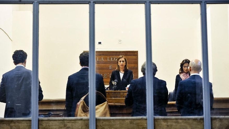 Judge Daniela Monaco Crea reads the sentence in the trial against ship captain Mohammad Ali Malek and crew mate Mahmud Bikhit in the April 2015 migrant sinking off Libya that left 700 people dead in the Mediterranean's worst-known migrant disaster, in Catania, Italy, Tuesday, Dec. 13, 2016. (AP Photo/Salvatore Cavalli)
