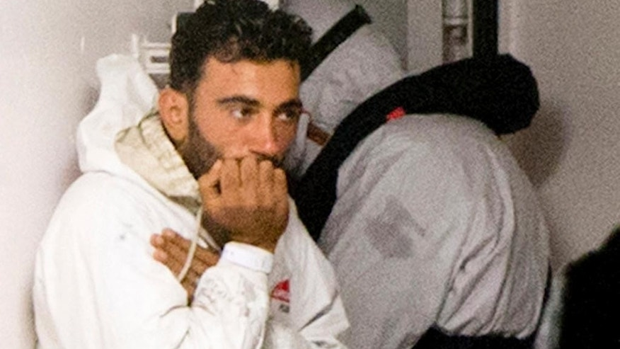 FILE - In this Monday, April 20, 2015, file photo, the Tunisian navigator Mohammed Ali Malek, and one of the survivors of the boat that overturned off the coast of Libya, waits to disembark from Italian Coast Guard ship Bruno Gregoretti, at the Sicilian harbor of Catania, southern Italy. A judge in Sicily on Tuesday, Dec. 13, 2016, convicted Malek and crew mate Mahmud Bikhit in the April 2015 sinking off Libya that left 700 people dead in the Mediterranean's worst-known migrant disaster. (AP Photo/Alessandra Tarantino, File)