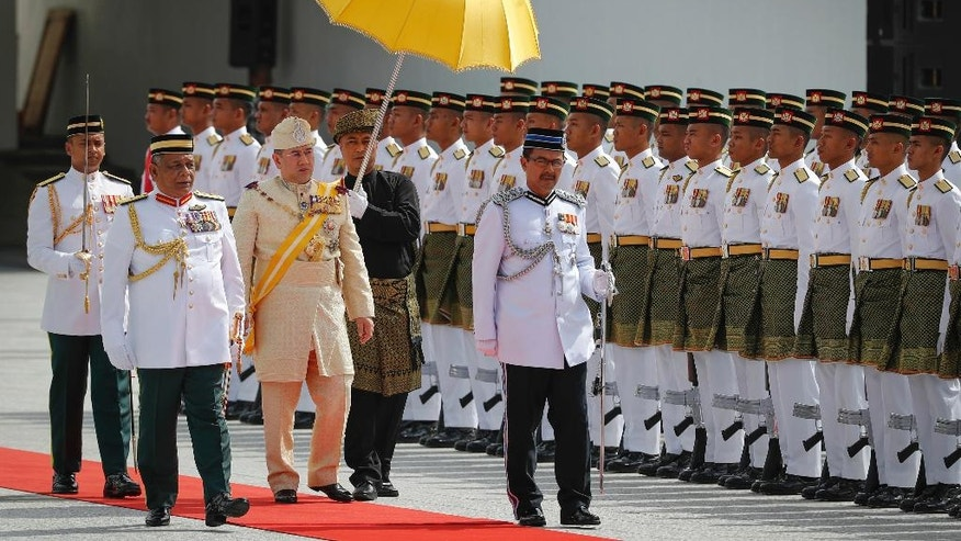 Sultan Muhammad V, third from left, inspects a ceremonial guard of honor during his welcome ceremony in Kuala Lumpur, Malaysia, Tuesday, Dec. 13, 2016. Sultan Muhammad V of Kelantan will serve a five-year term as King of Malaysia from Tuesday. (AP Photo/Vincent Thian)
