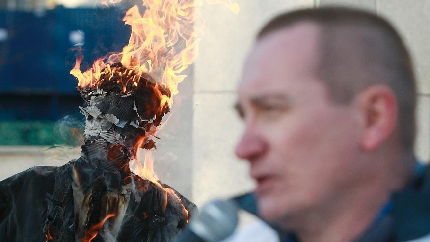 A government opponent burns an effigy of Jaroslaw Kaczynski, the powerful head of Poland's ruling conservative Law and Justice party before the parliament building in Warsaw, Poland, Tuesday, Dec. 13, 2016, the 35th anniversary of the imposition of martial law clampdown. The man protests the ruling party's policy saying it does not protect families in trouble. (AP Photo/Czarek Sokolowski)