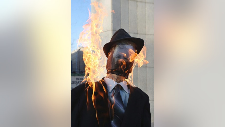 An effigy of Jaroslaw Kaczynski, the powerful head of Poland's ruling conservative Law and Justice party is burning before the parliament building in Warsaw, Poland, Tuesday, Dec. 13, 2016, the 35th anniversary of the imposition of martial law clampdown. A government opponent protests the ruling party's policy saying it does not protect families in trouble. (AP Photo/Czarek Sokolowski)