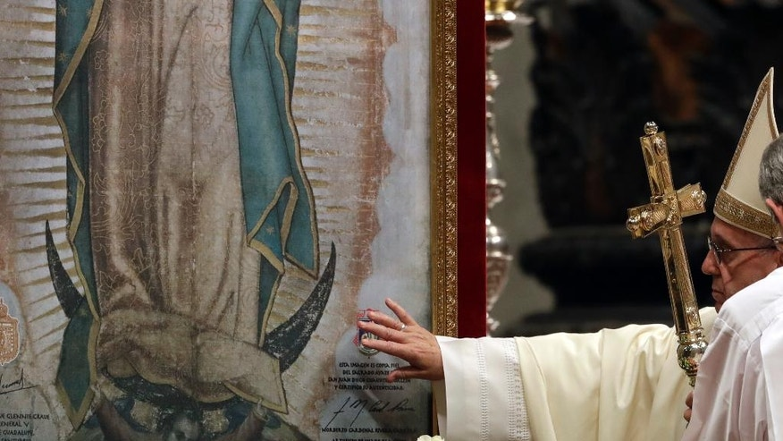 Pope Francis touches a portrait of Our Lady of Guadalupe as he celebrates a Mass in St. Peter's Basilica, at the Vatican, Monday, Dec. 12, 2016. (AP Photo/Gregorio Borgia)
