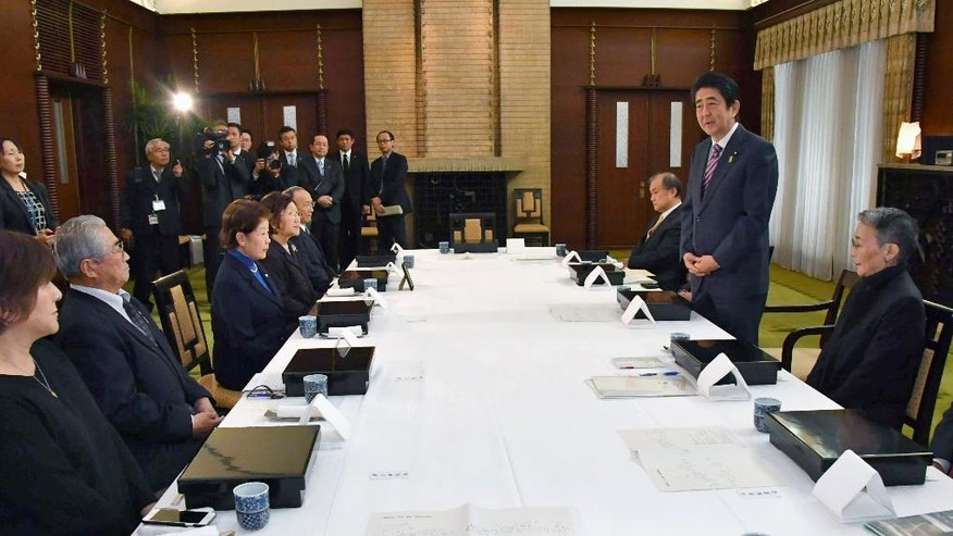 Japanese Prime Minister Shinzo Abe, second right, speaks to a group of former residents of the Russian-held islands off Japan's major northern island of Hokkaido during a meeting at the prime minister's official residence in Tokyo Monday, Dec. 12, 2016. The meeting was held three days before Abe's meeting with Putin in Japan later in the week. A dispute over the southern Kuril islands, which Japan calls the Northern Territories, has kept the two countries from signing a peace treaty formally ending their World War II hostilities. The Soviet Union seized them in the war's final days. (Kyodo News via AP)