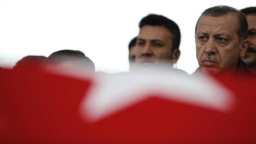 Turkey's President Recep Tayyip Erdogan attends the funeral prayers for police officer Hasim Usta, who was killed with dozens others late Saturday outside the Besiktas football club stadium Vodafone Arena, in Istanbul, Monday, Dec. 12, 2016. Turkey's police rounded up more than 100 members of a Kurdish political party on Monday as the country mourned the dozens killed in a bombing attack near an Istanbul soccer stadium. Turkish authorities have banned distribution of images relating to the Istanbul explosions within Turkey.(AP Photo/Emrah Gurel)