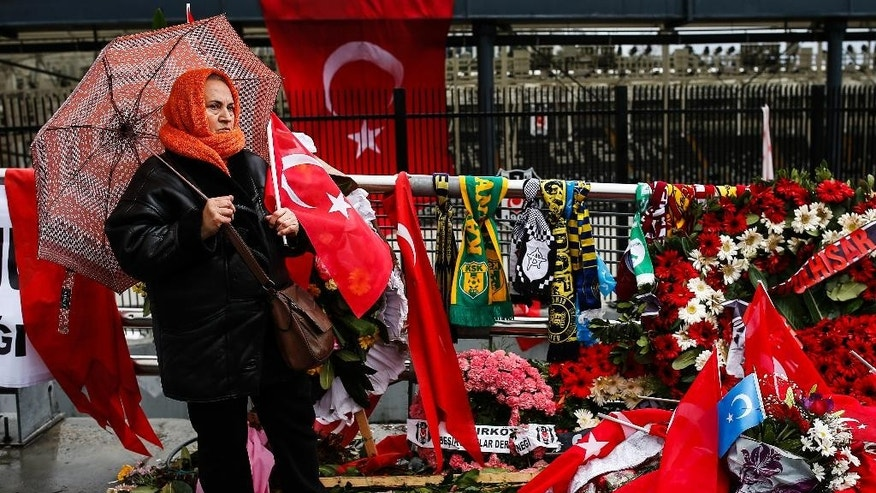 A Turkish woman looks around at the flags, flowers and scarves as she visits the Besiktas football club stadium Vodafone Arena in Istanbul, Tuesday, Dec. 13, 2016. Turkey launched a full investigation and started  burying the  dead Monday after two bombings in Istanbul killed dozens of people and wounded score others near Besiktas' stadium. Turkish authorities have banned distribution of images relating to the Istanbul explosions within Turkey.(AP Photo/Emrah Gurel)