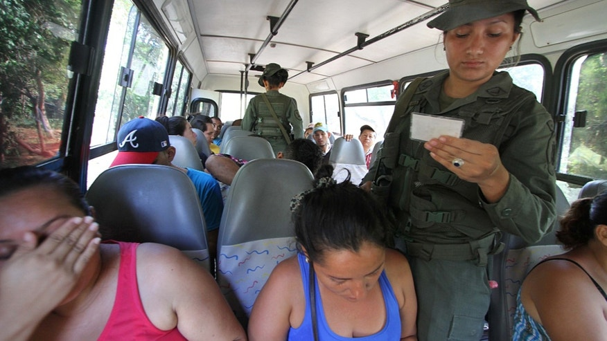 Venezuelan soldiers check the ID cards at a checkpoint along the border with Colombia.