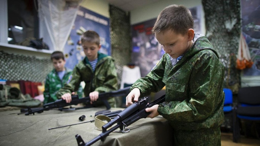 In this photo taken on Friday, Oct. 28, 2016, Alexander Yadryshnikov, 10, front, and his friends past apart Kalashnikov rifles as part of training in Verkhnyaya Pyshma, just outside Yekaterinburg, Russia. The training has been run by Yunarmia (Young Army), an organization sponsored by the Russian military that aims to encourage patriotism among the Russian youth. (AP Photo/Alexander Zemlianichenko)