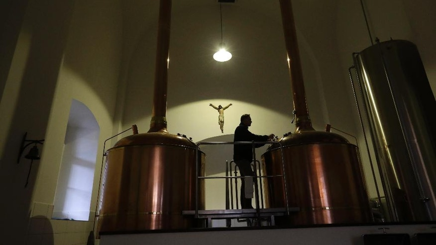 In this picture taken on Tuesday, Dec. 6, 2016, master brewer Jiri Kratochvil looks into a beer kettle at a brewery located inside a 12th century complex of the Zeliv monastery in Zeliv, Czech Republic. Once badly decimated by the former Communist regime the Catholic Church in the Czech Republic has been taking steps to become self-sufficient following a grand restitution deal. (AP Photo/Petr David Josek)