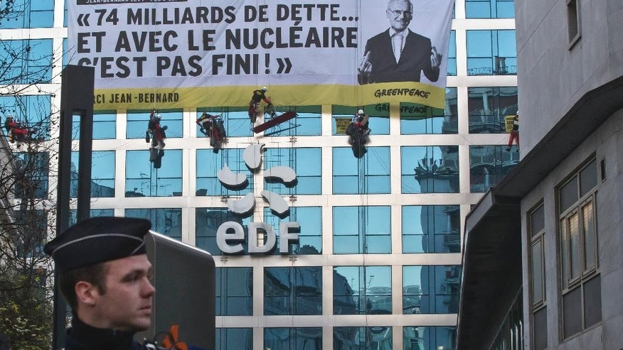 "Members of the group Greenpeace unfurl a banner on the building of the energy giant EDF during a nuclear protest in Paris, Wednesday, Dec. 14, 2016. Banner with the photo of the CEO of EDF Jean-Bernard Levy reads, ""74 billions in debt with nuclear power it's not finished"". Dozens of Greenpeace protesters are blocking the Paris headquarters of EDF, the public electricity company which operates the nuclear power plants in France. (AP Photo/Michel Euler)"