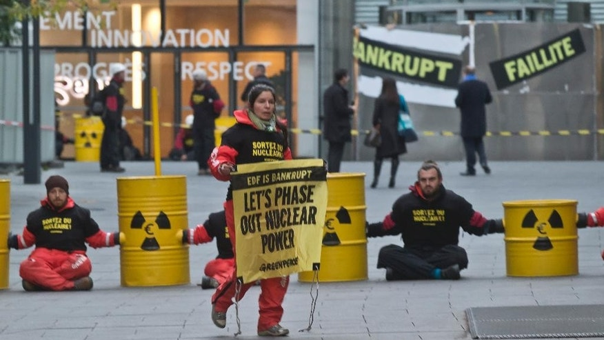 A Greenpeace activist walks with a banner outside the building of the energy giant EDF during a nuclear protest in Paris, Wednesday, Dec. 14, 2016. Dozens of Greenpeace protesters are blocking the Paris headquarters of EDF, the public electricity company which operates the nuclear power plants in France. (AP Photo/Michel Euler)