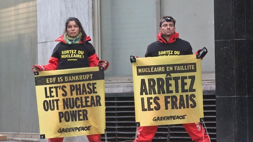 Members of the group Greenpeace stage a protest outside the building of the energy giant EDF in Paris, Wednesday, Dec. 14, 2016. Dozens of Greenpeace protesters are blocking the Paris headquarters of EDF, the public electricity company which operates the nuclear power plants in France. (AP Photo/Michel Euler)