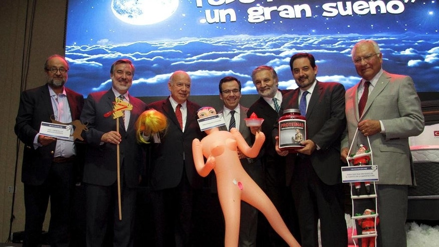 "CORRECTS SPELLING OF BITRAN - ProChile Director Roberto Paiva, from left to right, Chilean Sen. and ruling party presidential hopeful Alejandro Guillier, former OAS General Secretary Jose Miguel Insulza, Chile's Economy Minister Luis Cespedes, Ministry of Planning Executive Secretary Eduardo Bitran, Energy Minister Andres Rebolledo and Asimet President Juan Carlos Martinez, pose for a photo with a gift of an inflated sex toy, a placard taped over its mouth that reads in Spanish: ""To stimulate the economy"",  during the Asexma exporters' association annual dinner, in Santiago, Chile,  Monday, Dec. 13, 2016. Politicians and businessmen laughed and posed for the cameras, but later social networks exploded in criticism that pointed to the sexist nature of the gift. (AP Photo/Jorge Cadenas)"