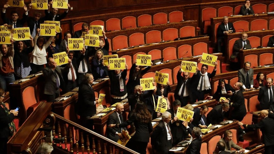 "Opposition lawmakers hold up signs with writing reading in Italian ""20 MILLION NO"" ahead of a confidence vote for Premier Paolo Gentiloni's government, at the Senate, in Rome, Wednesday, Dec. 14, 2016. On Tuesday his government won a vote of confidence at the Lower Chamber, approval from both houses is required for the government to carry on its mandate. At left is Foreign Minister Angelino Alfano. (AP Photo/Gregorio Borgia)"