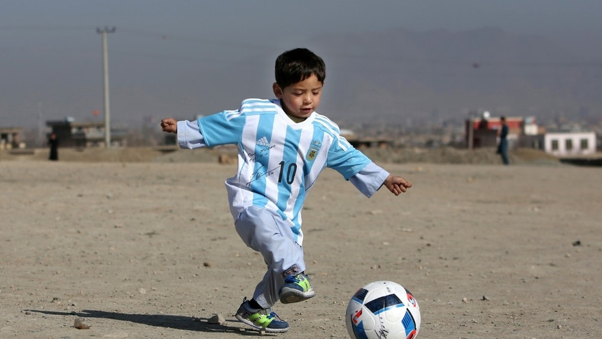 Murtaza Ahmadi, a five-year-old Afghan Lionel Messi fan playing with a soccer ball during a photo opportunity in Kabul, Afghanistan