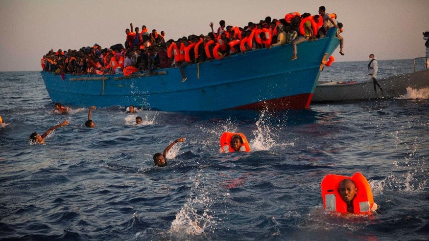 FILE - In this Monday, Aug. 29, 2016 file photo, migrants, most of them from Eritrea, jumps onto the water from a crowded wooden boat as they are helped by members of an NGO during a rescue operation at the Mediterranean sea, about 13 miles north of Sabratha, Libya.(AP Photo/Emilio Morenatti, File)