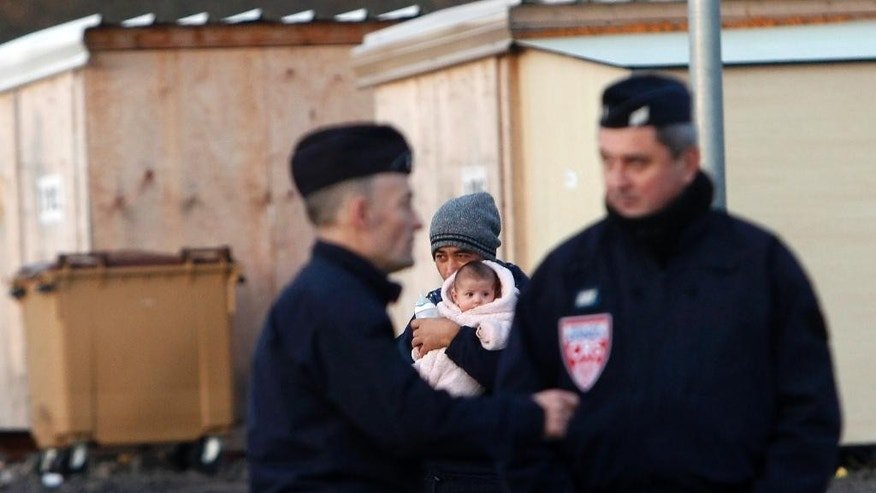 A migrant from Afghanistan holds a child at the migrants camp built by Doctors Without Borders in Grande Synthe, outside Dunkirk, northern France, Wednesday, Dec. 14, 2016. (AP Photo/Michel Spingler)