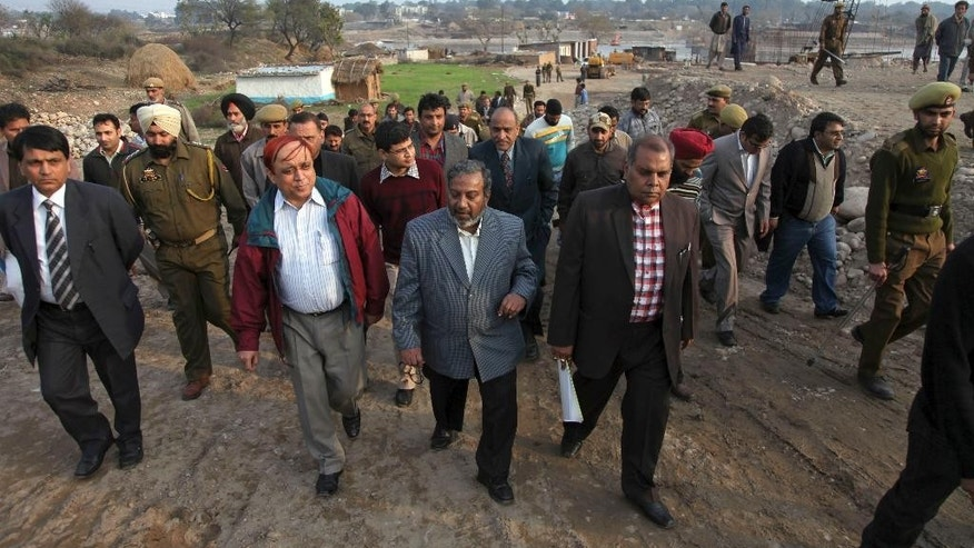 FILE - In this Sunday, Feb. 20, 2011 file photo, Pakistan's Indus water commission official, Shiraj Mamon, center left in red jacket, walks with Indian officials on the banks of the river Tawi in Jammu, India. Officials say on Wednesday, Dec. 14, 2016 Pakistani and Indian experts are expected to resume talks over the construction of two controversial hydropower projects by India on Indus river system, the only source of water for Pakistan's agriculture-based economy. (AP Photo/Channi Anand)