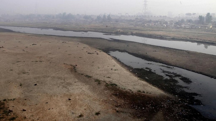 Very little water flows in the Ravi River in Lahore, Pakistan, Wednesday, Dec. 14, 2016. Under the Indus Water Treaty, India has exclusive rights to three Indus basin rivers, including the Ravi, which has virtually disappeared on the Pakistani side. Pakistani and Indian officials said Wednesday they would consider resuming direct talks over water sharing after the World Bank halted a process to arbitrate a longstanding dispute over two Indian hydroelectric projects. (AP Photo/K.M. Chaudary)