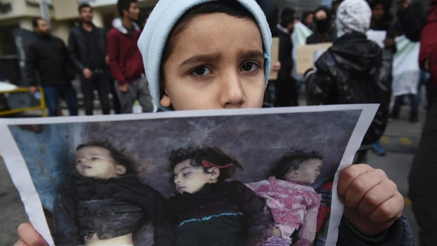 A Syrian boy holds a photo depicting dead children during a protest near the Russian Consulate, at the northern Greek city of Thessaloniki, Wednesday, Dec. 14, 2016. A few dozens of Syrian refugees, who live in camps around the city, staged a rally to protest against Russia's military interference in Syria. (AP Photo/Giannis Papanikos)