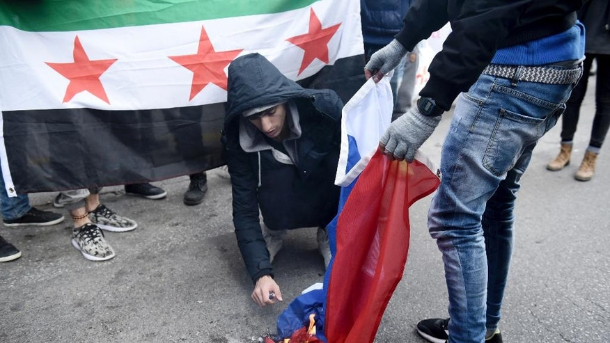 Syrian refugees burn a Russian flag during a protest near the Russian Consulate, at the northern Greek city of Thessaloniki, Wednesday, Dec. 14, 2016. A few dozens of Syrian refugees, who live in camps around the city, staged a rally to protest against Russia's military interference in Syria. (AP Photo/Giannis Papanikos)