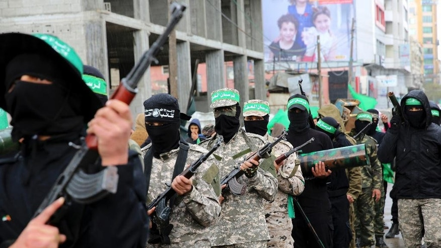 Masked Palestinian militants from the Izzedine al-Qassam Brigades, a military wing of Hamas, commemorate the 29th anniversary of their group, in Gaza City, Wednesday, Dec. 14, 2016. Tens of thousands of Palestinians, including hundreds of gunmen, rallied in Gaza in support of the militant Islamic group Hamas that rules the territory. Hamas overtook Gaza by force in 2007 after routing troops loyal to Palestinian President Mahmoud Abbas in bloody street battles. Palestinians have been divided since between Gaza under Hamas and Abbas governing parts of the West Bank. (AP Photo/Adel Hana)