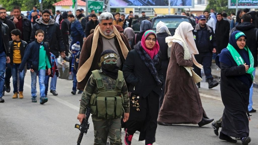 A masked Palestinian boy wears a uniform and holds a toy weapon during a rally to commemorate the 29th anniversary of the founding of Hamas, in Gaza City, Wednesday, Dec. 14, 2016. Tens of thousands of Palestinians, including hundreds of gunmen, rallied in Gaza in support of the militant Islamic group Hamas that rules the territory. Hamas overtook Gaza by force in 2007 after routing troops loyal to Palestinian President Mahmoud Abbas in bloody street battles. Palestinians have been divided since between Gaza under Hamas and Abbas governing parts of the West Bank. (AP Photo/Adel Hana)