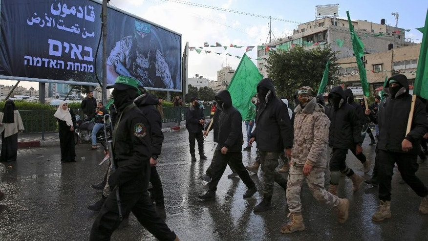 "Masked Palestinian militants from the Izzedine al-Qassam Brigades, a military wing of Hamas, march next to a billboard with Arabic and Hebrew text that reads, ""we are coming from under the ground,"" during a rally to commemorate the 29th anniversary of their group, in Gaza City, Wednesday, Dec. 14, 2016. Hamas overtook Gaza by force in 2007 after routing troops loyal to Palestinian President Mahmoud Abbas in bloody street battles. Palestinians have been divided since between Gaza under Hamas and Abbas governing parts of the West Bank. (AP Photo/Adel Hana)"